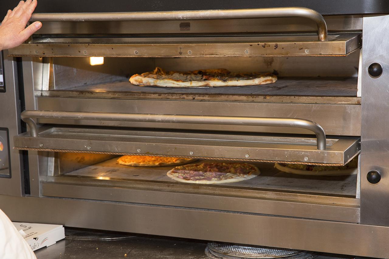 XL och standardpizza i ugn för gräddning.